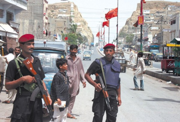 Street strife: police keep watch in an area of Karachi in June amid tensions between the two main political and ethnic  groupings. Those form the chief cause of friction in what is a relatively liberal and secular city. Source: Eyevine