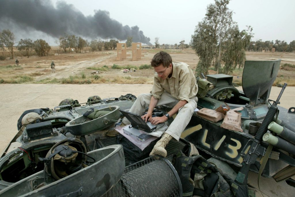 Reuterís journalist Matthew Green works on the top of an Amphibia Assault Vehicle on the road near Baghdad on April 8, 2003.    REUTERS/Oleg Popov